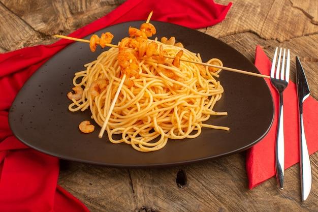 Gotowany włoski makaron z krewetkami wewnątrz brązowego talerza ze sztućcami na drewnie