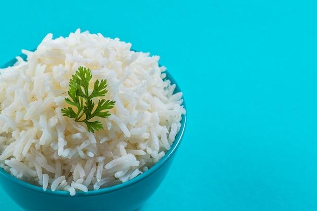 Gotowany zwykły biały ryż basmati z kolendrą w niebieskiej misce