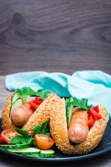 Gotowe do spożycia hot dogi ze smażonych kiełbasek, bułek sezamowych i świeżych warzyw na talerzu na drewnianym stole