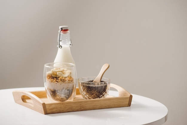 Gotowe do zjedzenia zdrowe i pożywne śniadanie - granola z migdałami, nasionami chia, owocami bananowymi i kiwi oraz jagodami i słoikiem z mlekiem w pobliżu