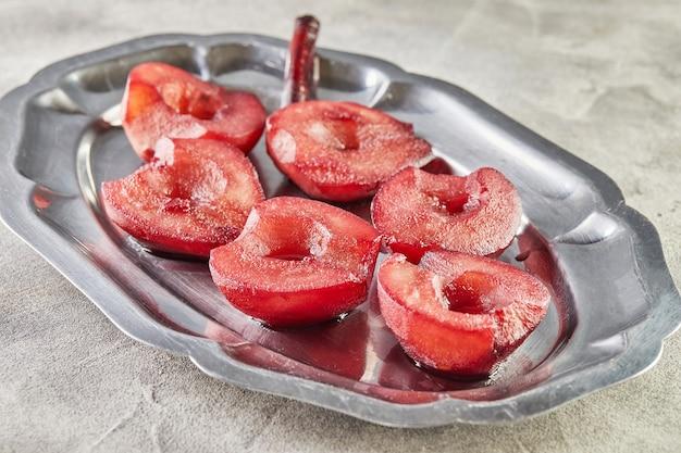 Gotowe gruszki, gotowane w czerwonym syropie z winem, na tacy do podania gościom.