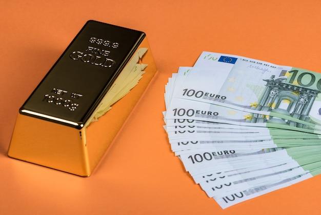 Gotówka euro i sztabka złota na pomarańczowej powierzchni. banknoty pieniądze. rachunek. wlewek. bajorek.