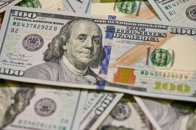 Gotówka stu dolarowych banknotów finansowych inwestycji biznesowych i ekonomicznej koncepcji pieniędzy na tle .
