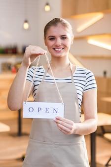 Gotowy dla gości. radosna, miła, pozytywna kobieta uśmiecha się i patrzy na ciebie podczas otwierania swojej kawiarni