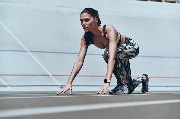 Gotowy do biegu. piękna młoda kobieta w odzieży sportowej stojąca na linii startu