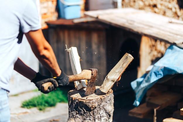 Gotowy do cięcia drewna. zakończenie siekiery tnąca bela podczas gdy inne notuje kłaść w tle