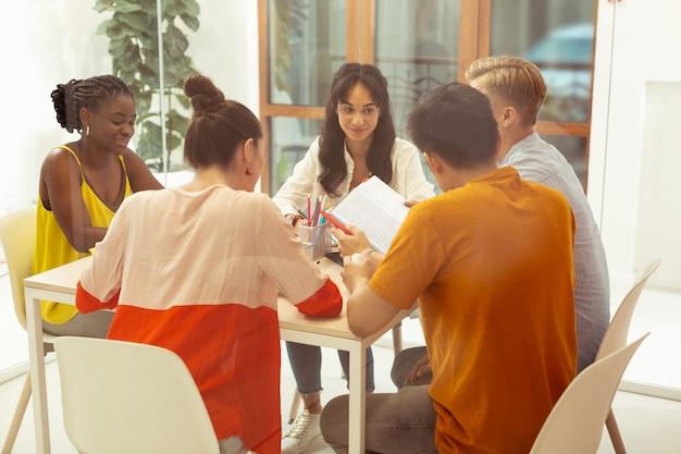 Gotowy do dyskusji. grupa młodych ludzi siedzących przy stole i wykonujących wspólnie zadanie domowe