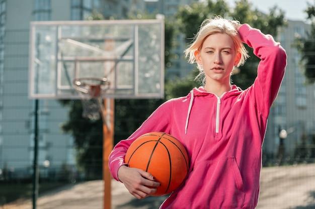 Gotowy do gry. miła blondynka kładąc rękę na głowie, będąc gotową do zabawy