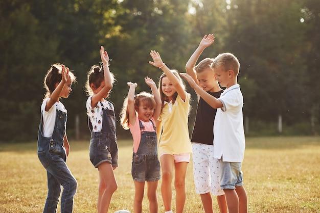 Gotowy do gry. młode sportowe dzieci stoi razem w polu w słoneczny dzień.