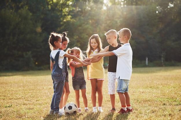 Gotowy do gry. młode sportowe dzieci z piłki nożnej stoi razem w polu w słoneczny dzień.
