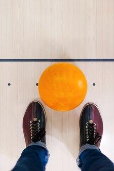 Gotowy do gry. zbliżenie kuli do kręgli leżącej w pobliżu ludzkich nóg