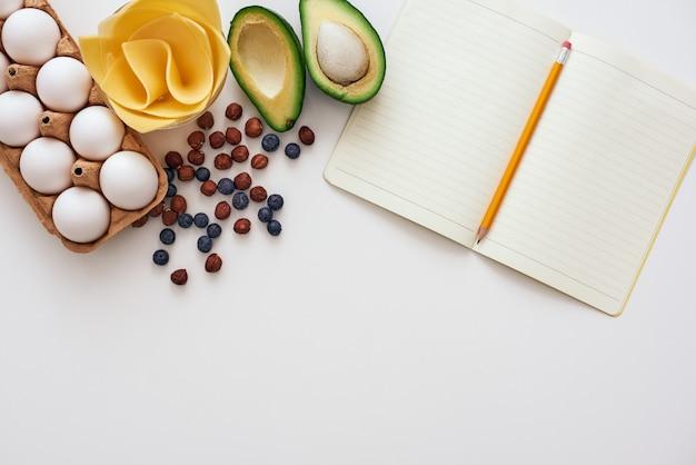 Gotowy do napisania przepisu. książka kucharska i jajka leżą na stole obok suszonych jagód, sera i awokado
