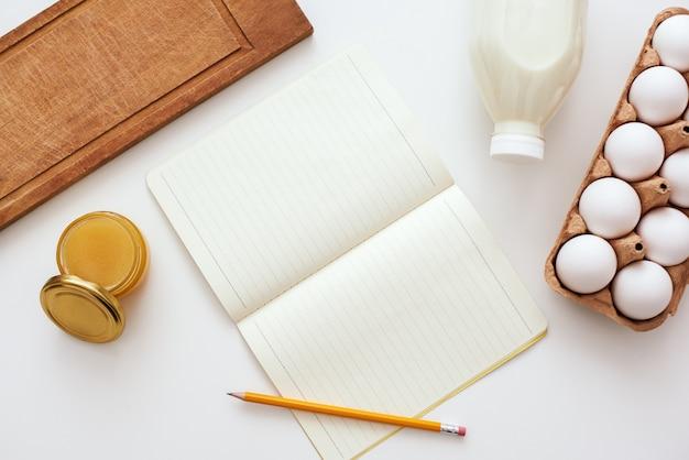 Gotowy do napisania przepisu. ołówek i książka kucharska leżą na stole obok mleka, miodu i jajek