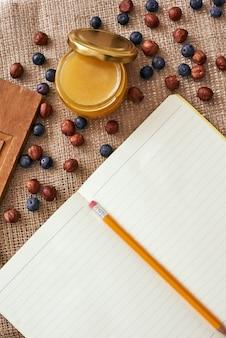 Gotowy do napisania przepisu. ołówek i książka kucharska leżą na stole obok suszonych jagód i miodu
