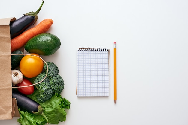 Gotowy do napisania przepisu. ołówek i notatnik leżą na stole w pobliżu świeżych i jasnych warzyw