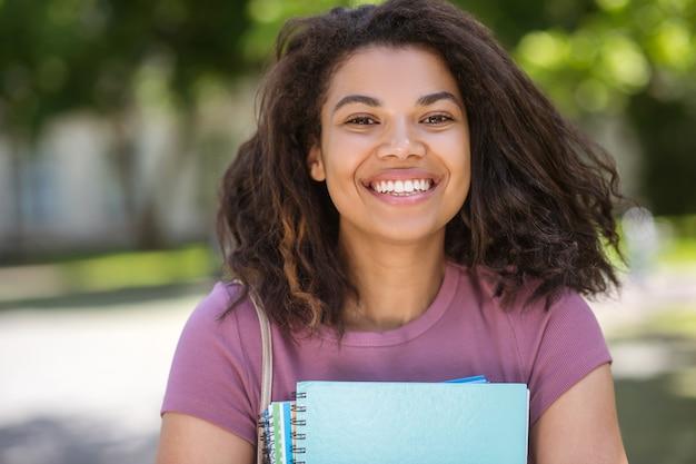 Gotowy do nauki. dziewczyna w różowej koszulce trzymająca podręczniki w dłoniach
