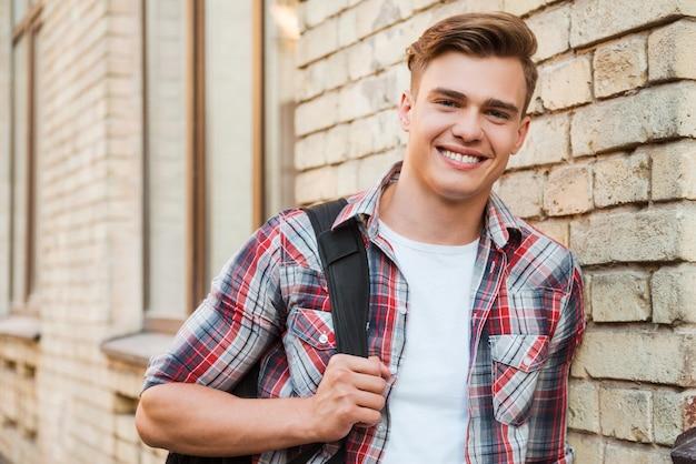 Gotowy do nauki. przystojny młody mężczyzna niosący plecak na jednym ramieniu i uśmiechający się, opierając się o ceglany mur