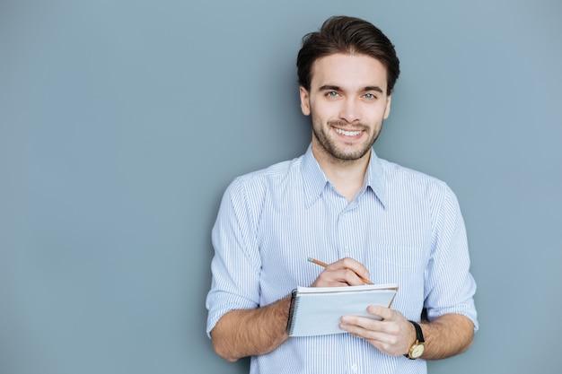 Gotowy do pisania. wesoły pozytywny kreatywny mężczyzna trzyma ołówek i uśmiecha się do ciebie, będąc gotowym do pisania
