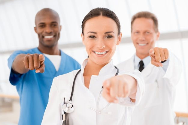 Gotowy do pomocy! trzech wesołych lekarzy wskazujących na ciebie i uśmiechających się