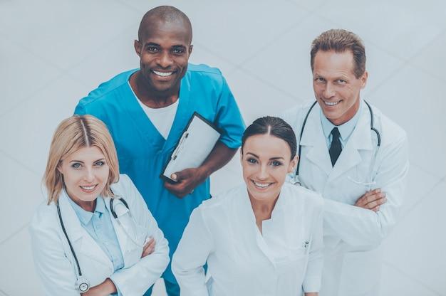 Gotowy do pomocy w każdej chwili. widok z góry czterech pewnych siebie lekarzy stojących blisko siebie i uśmiechniętych