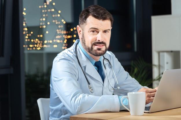 Gotowy do pracy. mądry miły lekarz mężczyzna siedzi przed laptopem i patrzy na ciebie, gdy jest gotowy do pracy