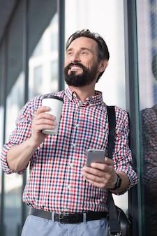Gotowy do pracy. przyjemny przystojny mężczyzna uśmiecha się stojąc w pobliżu budynku biurowego