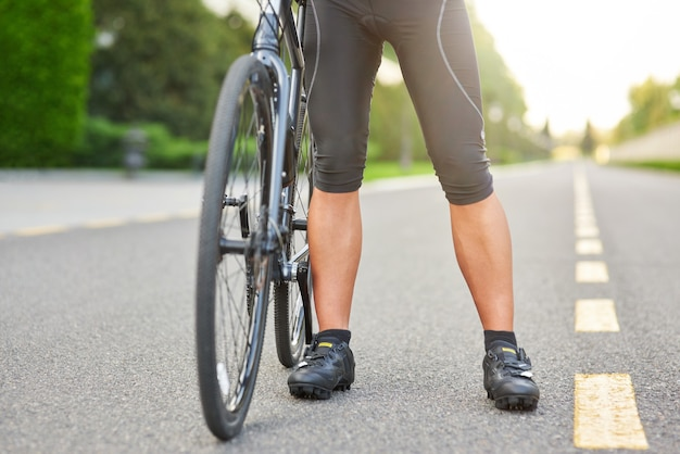 Gotowy do treningu przycięte zdjęcie profesjonalnego kolarza płci męskiego w spodenkach i butach rowerowych