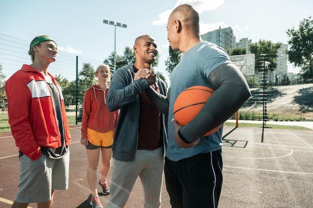 Gotowy do treningu. radosny szczęśliwy człowiek uśmiecha się podczas powitania swojego trenera koszykówki
