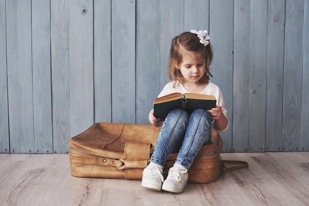 Gotowy do wielkiej podróży. szczęśliwa mała dziewczynka czyta ciekawą książkę niesie dużą teczkę i ono uśmiecha się. podróż, wolność i wyobraźnia