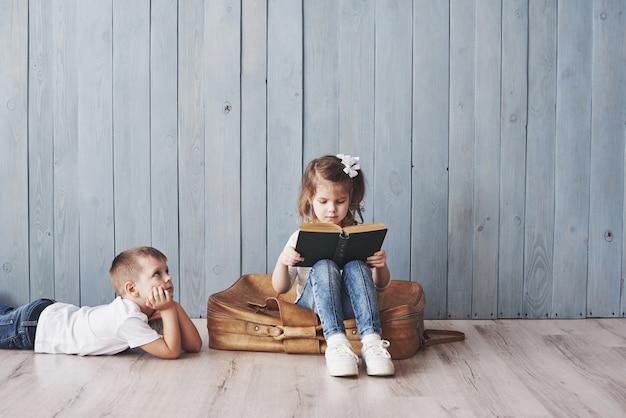 Gotowy do wielkiej podróży. szczęśliwa mała dziewczynka i chłopiec czyta ciekawą książkę niesie dużą teczkę i ono uśmiecha się. podróż, wolność i wyobraźnia