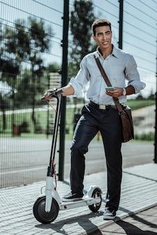 Gotowy do wyjścia. niespokojny facet uruchamia aplikację i stoi na skuterze elektrycznym