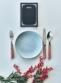 Gotowy do zamówienia. ujęcie pod dużym kątem pustego talerza, widelca, łyżki, noża i zamkniętego menu leżącego naprzeciw