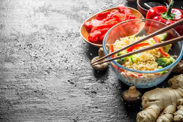 Gotowy makaron instant z brokułami, pieprzem i imbirem. na czarnym rustykalnym