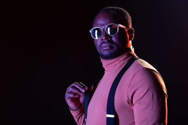 Gotowy na imprezę. uważny brodaty mężczyzna w stylowych okularach stojąc na czarnym tle