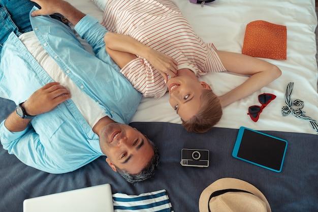 Gotowy na plażę. szczęśliwe małżeństwo powoli rozpakowuje swoje wakacyjne rzeczy leżące wśród nich na łóżku.