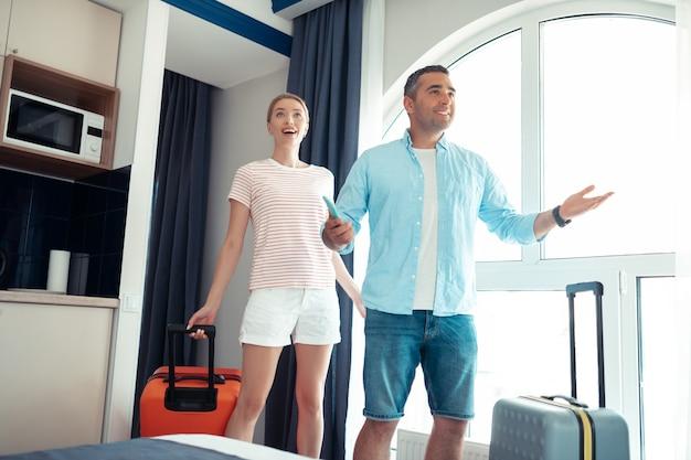 Gotowy na relaks. pod wielkim wrażeniem małżeństwo stojące przy dużym oknie, szczęśliwe ze swojego wynajętego mieszkania na wakacjach.