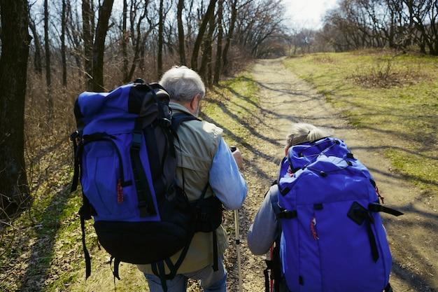 Gotowy na więcej. starsza rodzina para mężczyzna i kobieta w strój turystyczny spaceru na zielonym trawniku w pobliżu drzew w słoneczny dzień. pojęcie turystyki, zdrowego stylu życia, relaksu i wspólnoty.