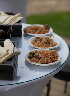 Gotowy pilaw i podany. narodowe danie kuchni orientalnej. lawasz, bułki i chleb. gotowe posiłki.