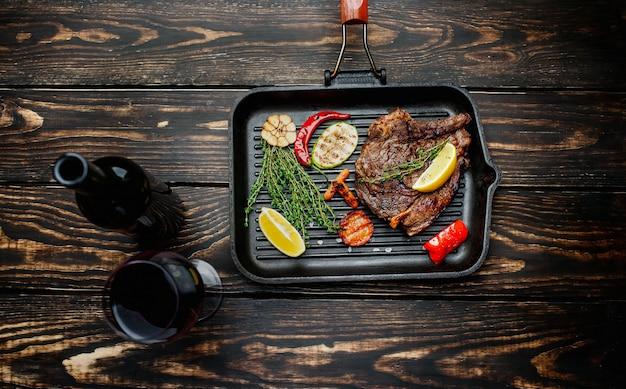 Gotowy stek wołowy z grillowanymi warzywami na patelni grillowej z przyprawami i butelką czerwonego wina ze szklanką na drewnianym tle