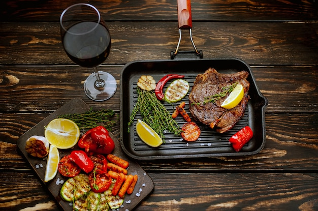 Gotowy stek wołowy z grillowanymi warzywami na patelni grillowej z przyprawami i lampką czerwonego wina na drewnianym tle