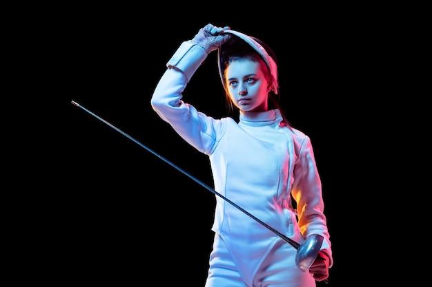 Gotowy. teen dziewczyna w stroju szermierki z mieczem w ręku na białym na czarnym tle, neon light. młoda modelka ćwicząca i trenująca w ruchu, w działaniu. copyspace. sport, młodość, zdrowy tryb życia.