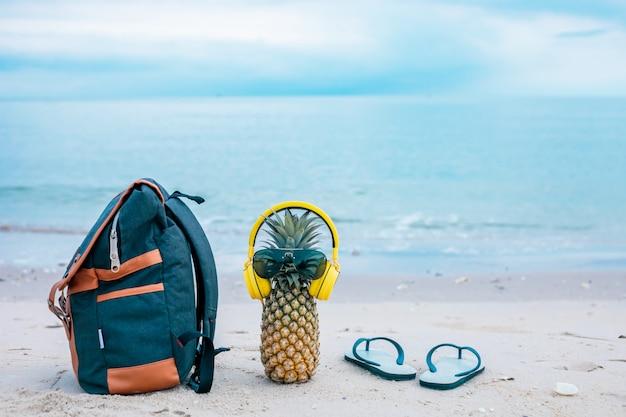 Gotuj atrakcyjnego ananasa w stylowych okularach przeciwsłonecznych, złotych torebkach i słuchawkach na piasku z turkusową wodą. koncepcja tropikalny wakacje