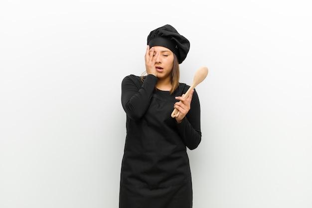 Gotuj kobietę znudzoną, sfrustrowaną i senną po męczącym, nudnym i żmudnym zadaniu, trzymając twarz ręką na białym