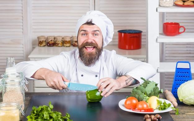 Gotuj pokrojone warzywa. gotowanie. cięcie i siekanie. przystojny brodaty kucharz w mundurze. składniki. profesjonalna kuchnia.