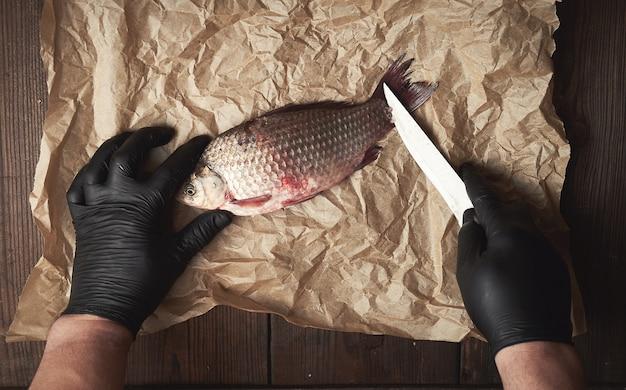 Gotuj w czarnych rękawiczkach czyści karpie z całych ryb