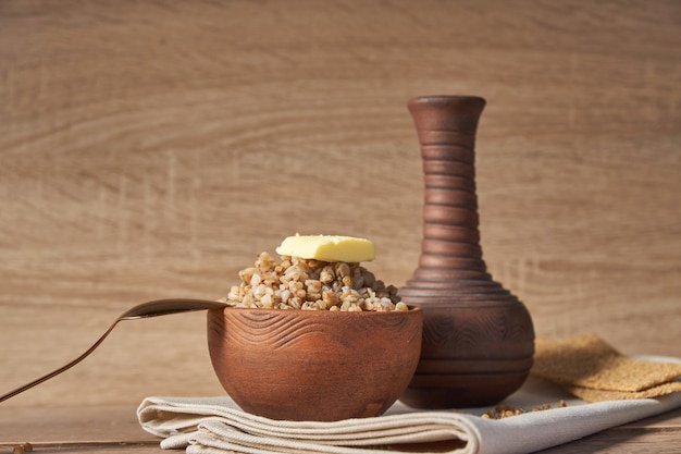 Gotujący gryczany zboże w brown glinianym pucharze na drewnianym stole. bezglutenowe ziarno dla zdrowej diety
