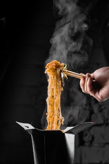 Gotujący na parze makaron ryżowy w pudełku woka na czarnej powierzchni