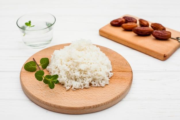 Gotujący ryż z datami owocowymi na drewnianej desce