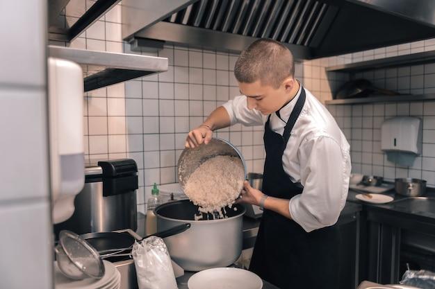 Gotujący się ryż. młody pracowity kucharz ubrany w czarny fartuch stołówki gotuje ryż na obiad