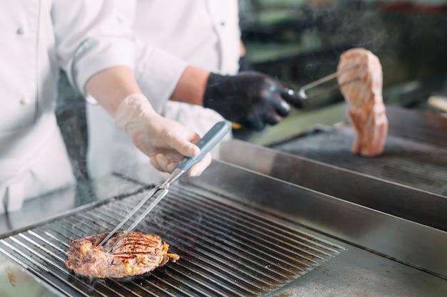 Gotuje pieczone mięso na kuchence w kuchni restauracji lub hotelu.